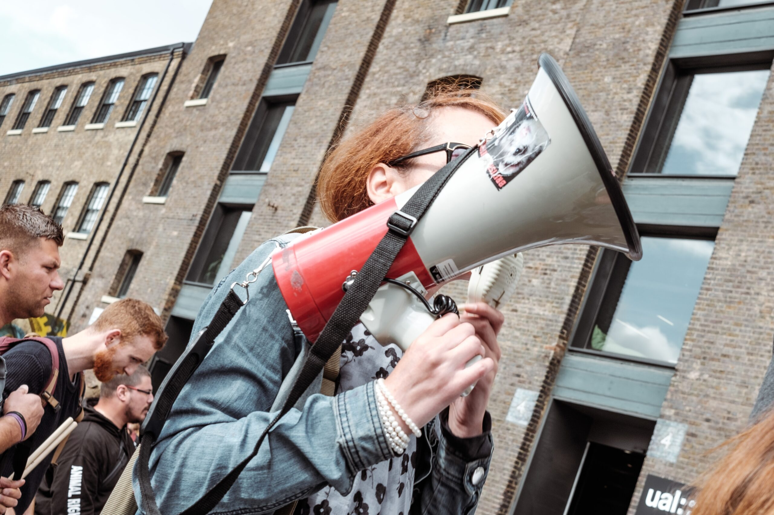 Person holding a megaphone at the front of a crowd
