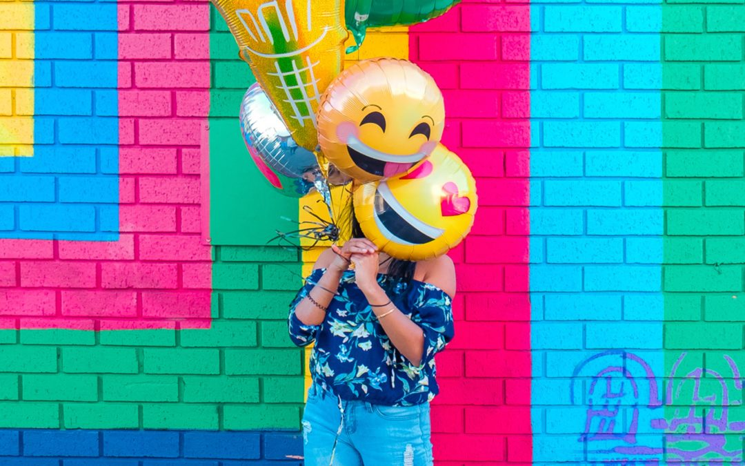 Person holding emoji balloons obscuring face standing in front of brightly painted exterior wall
