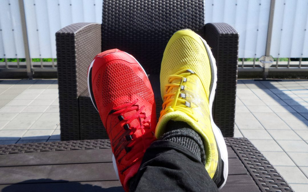 A pair of crossed feet up on a table wearing odd coloured trainers.