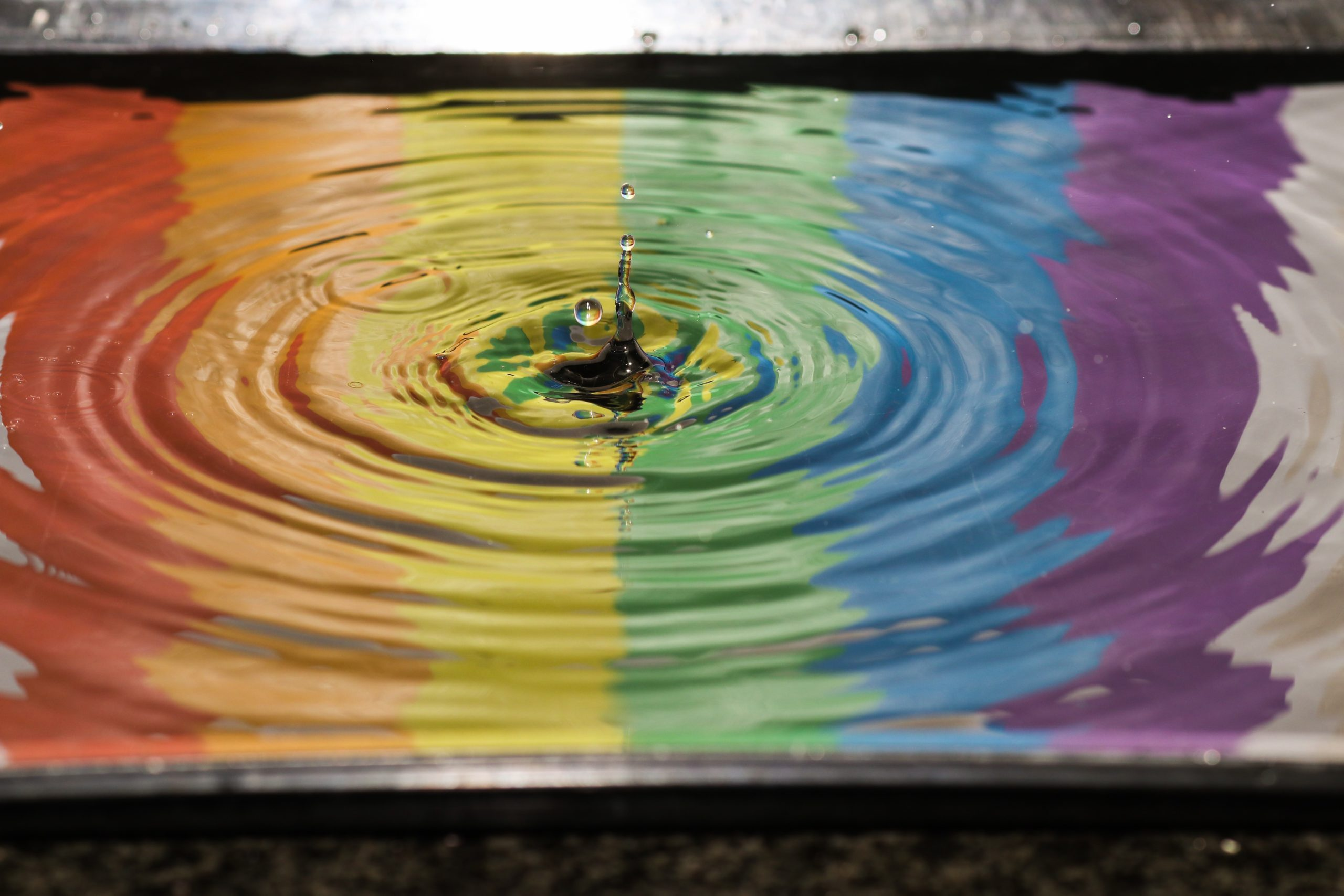 A drop of water in a puddle with a rainbow reflected in it