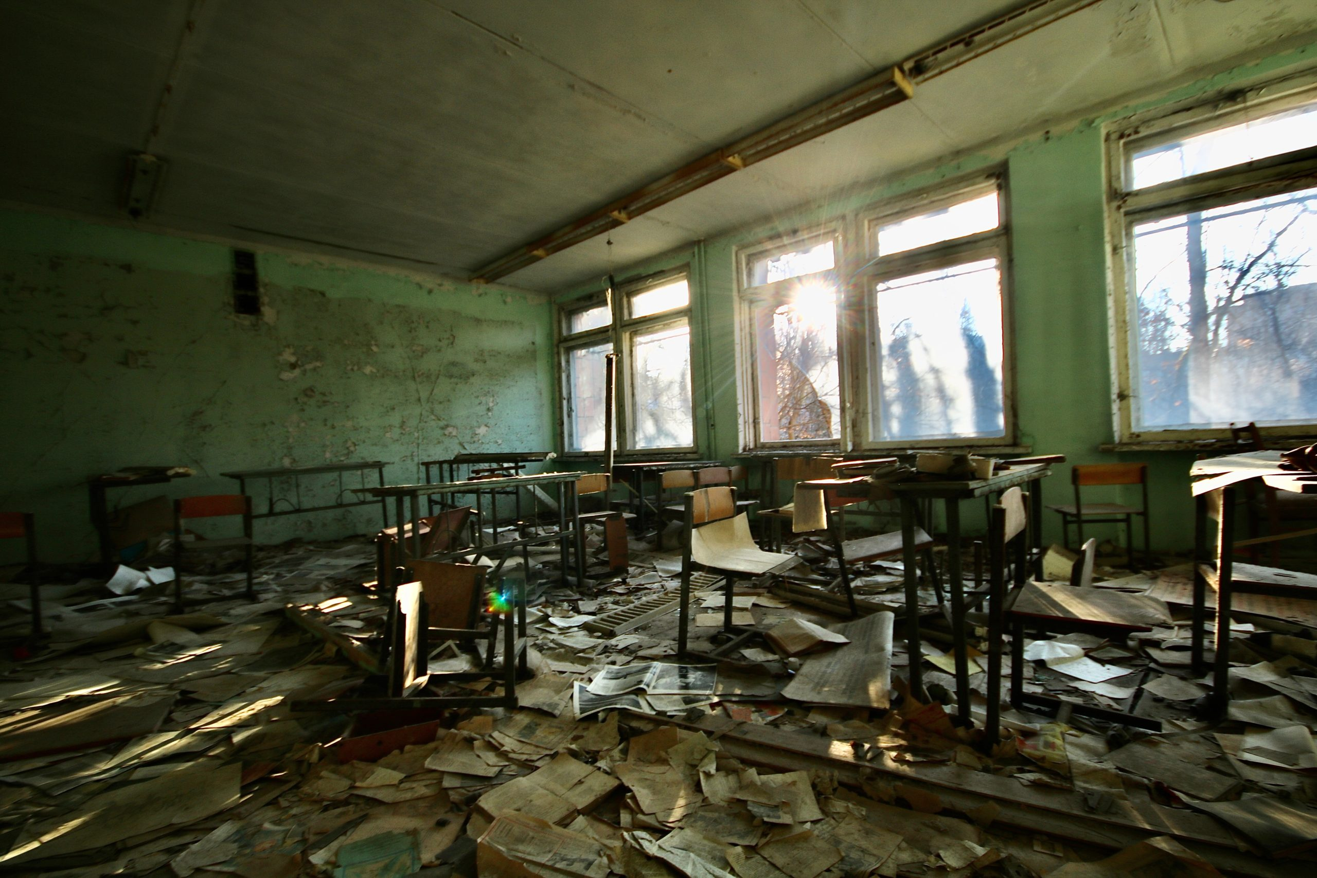 A deserted classroom in disarray with windows smashed, desks and chairs turned over the floor strewn with paapers