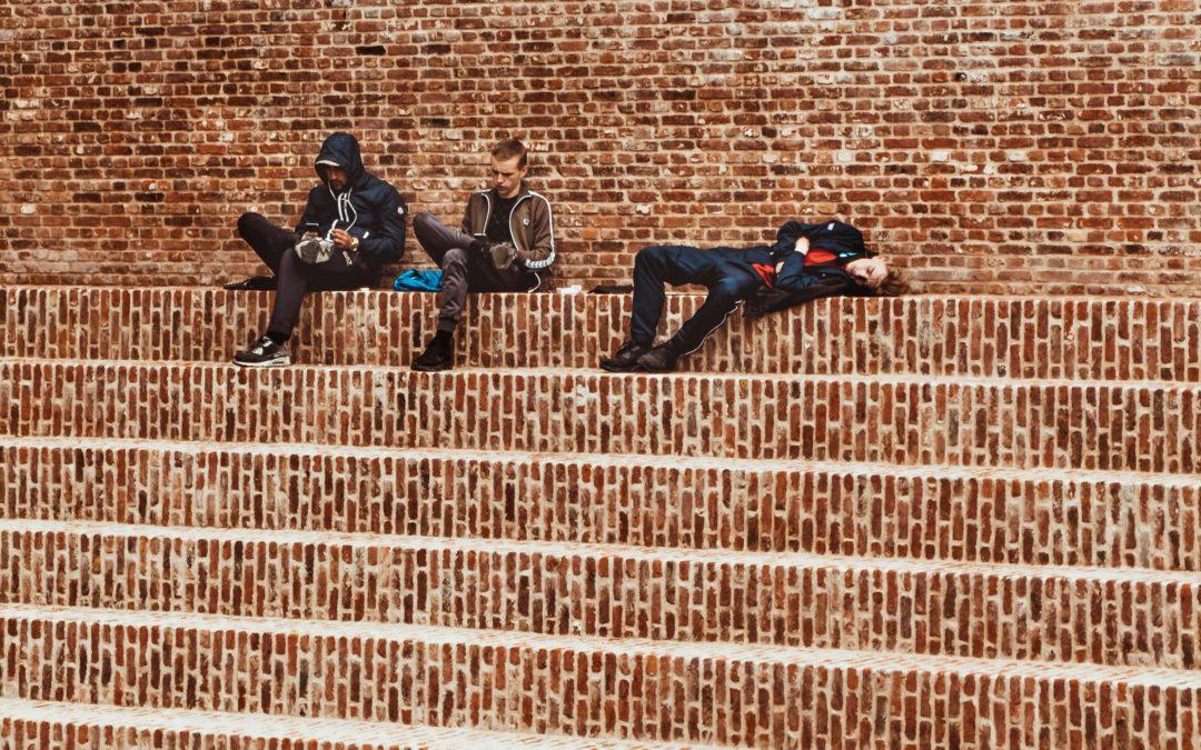 Three school children sitting on some brick steps looking bored.