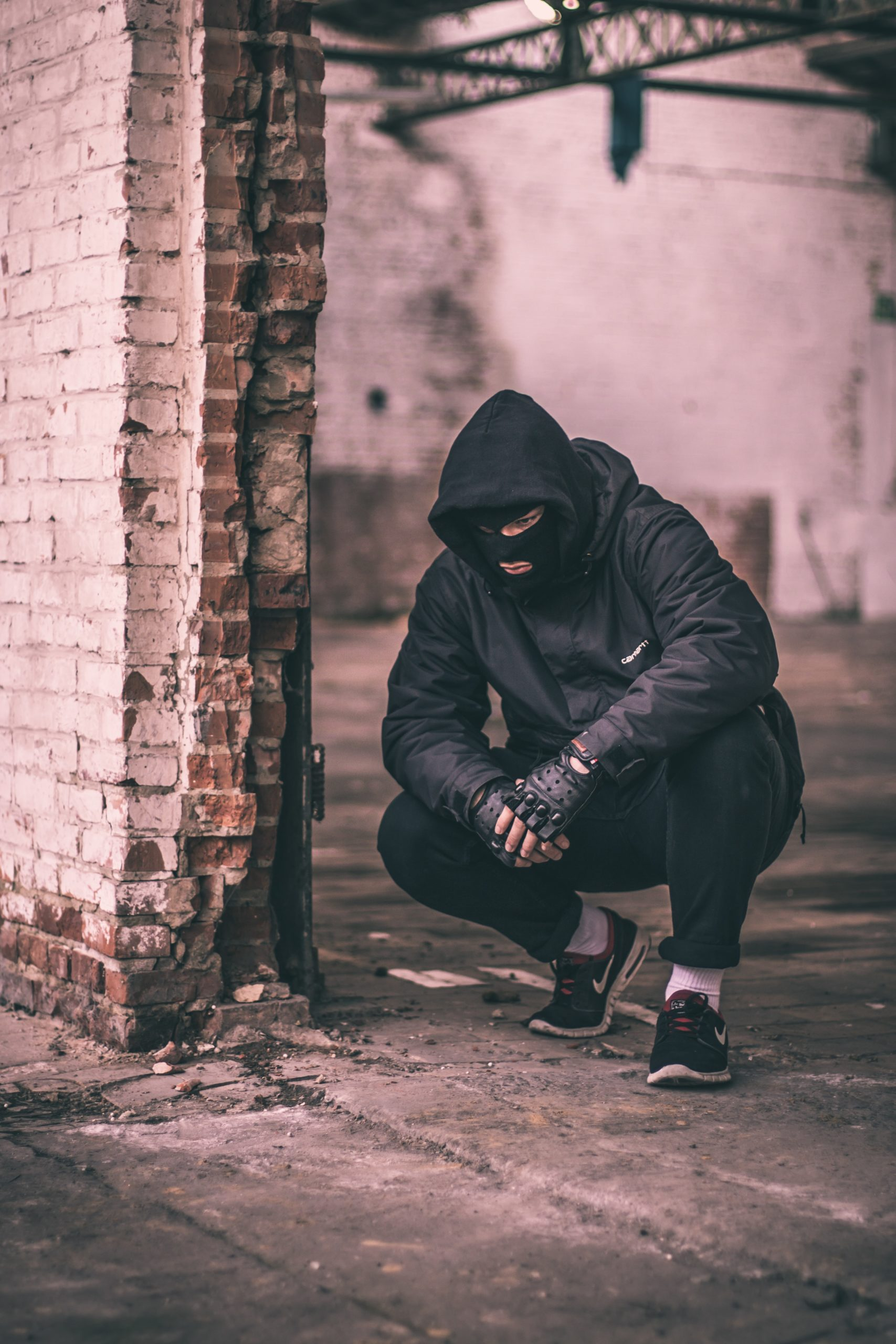 A man in a balaclava and hooded top crouching by a brick wall