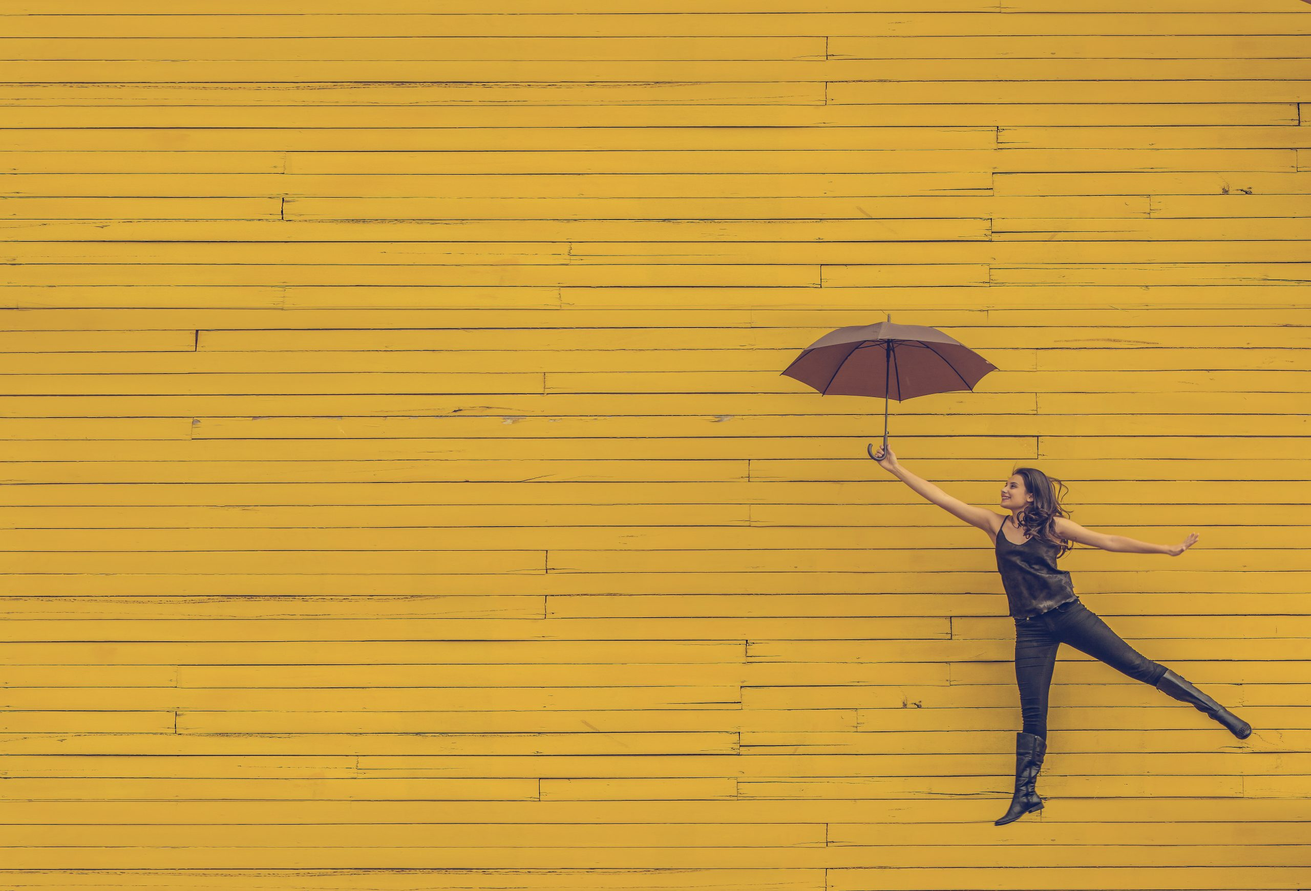 Woman holding an open umbrella in her outstretched arm against a background of yellow painted wooden boards
