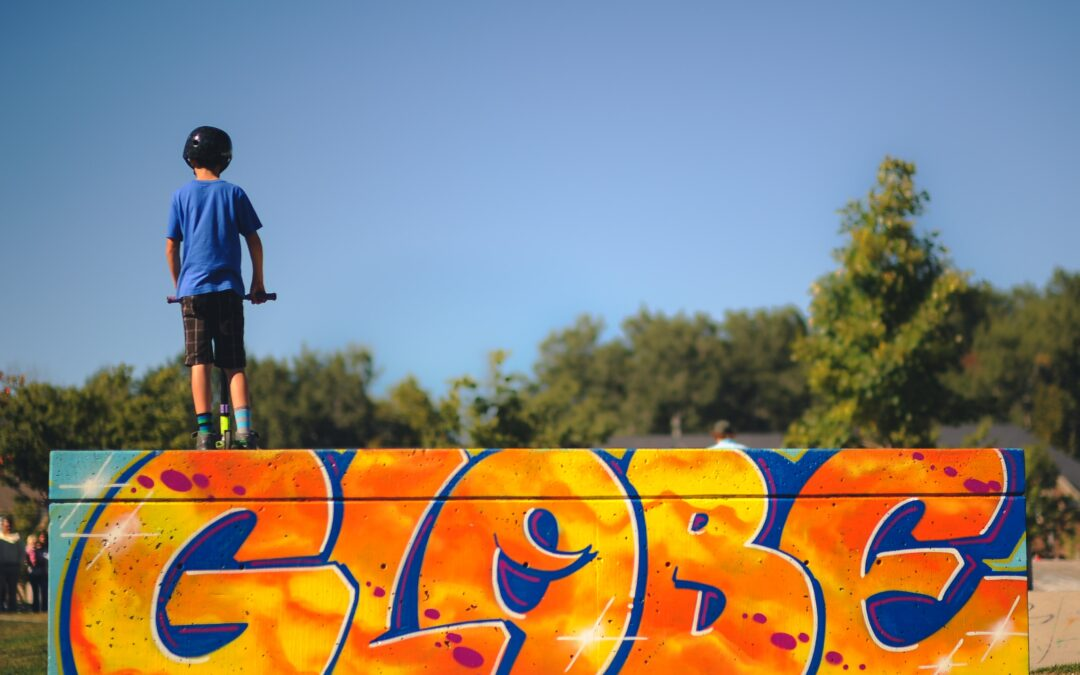 "Child with his back to the camera standing at the top of a skateboard ramp on a scooter, the ramp shows graffiti saying ""Globe"""