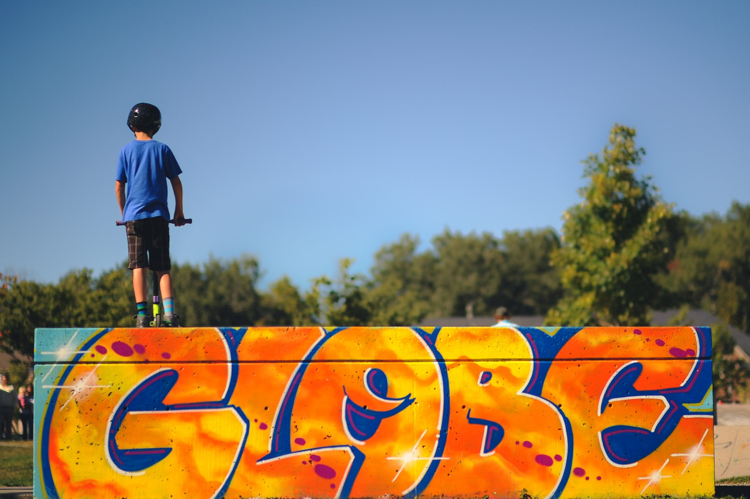 """Child with his back to the camera standing at the top of a skateboard ramp on a scooter, the ramp shows graffiti saying """"Globe"""""""