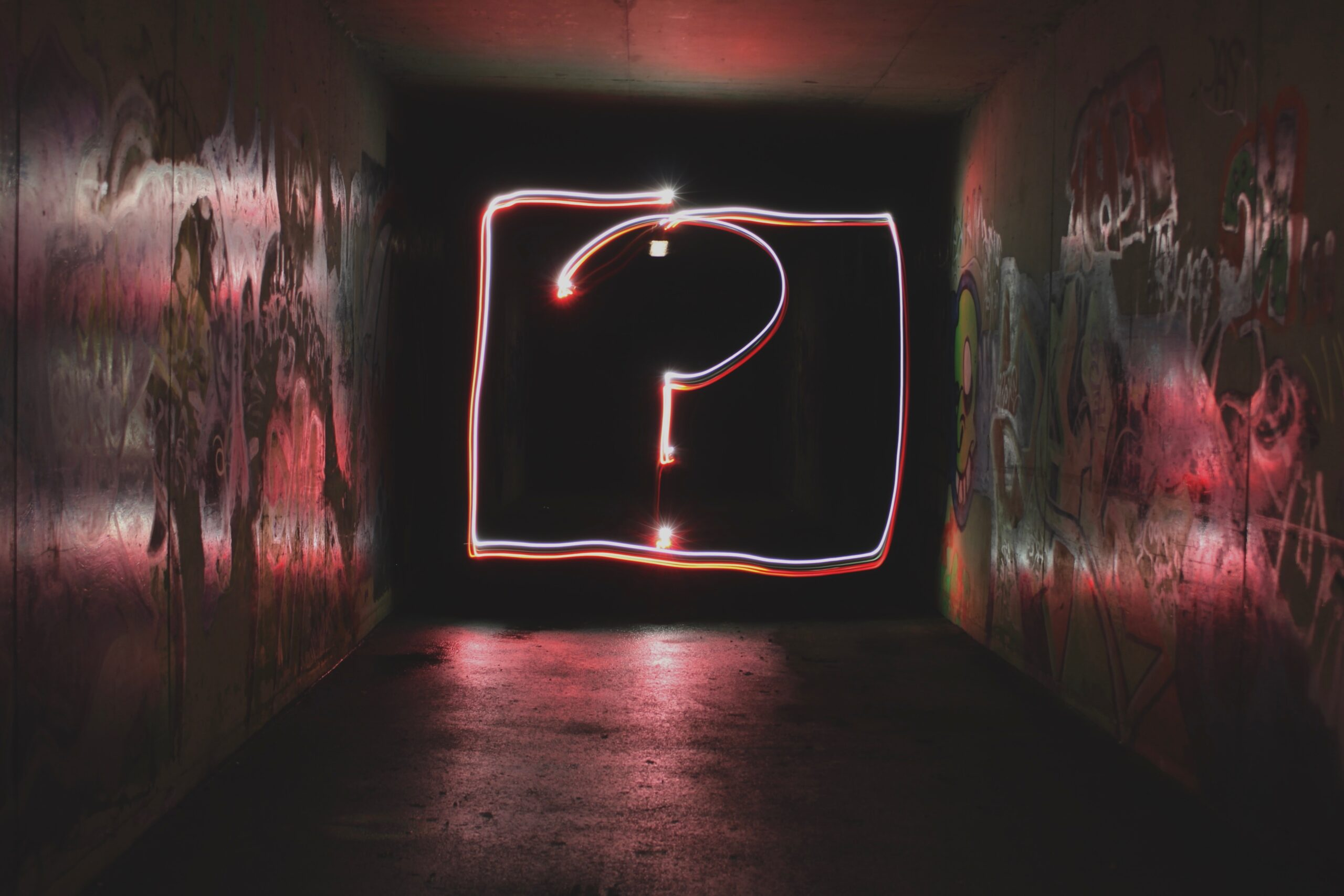 A question mark on the wall in neon in a dark room