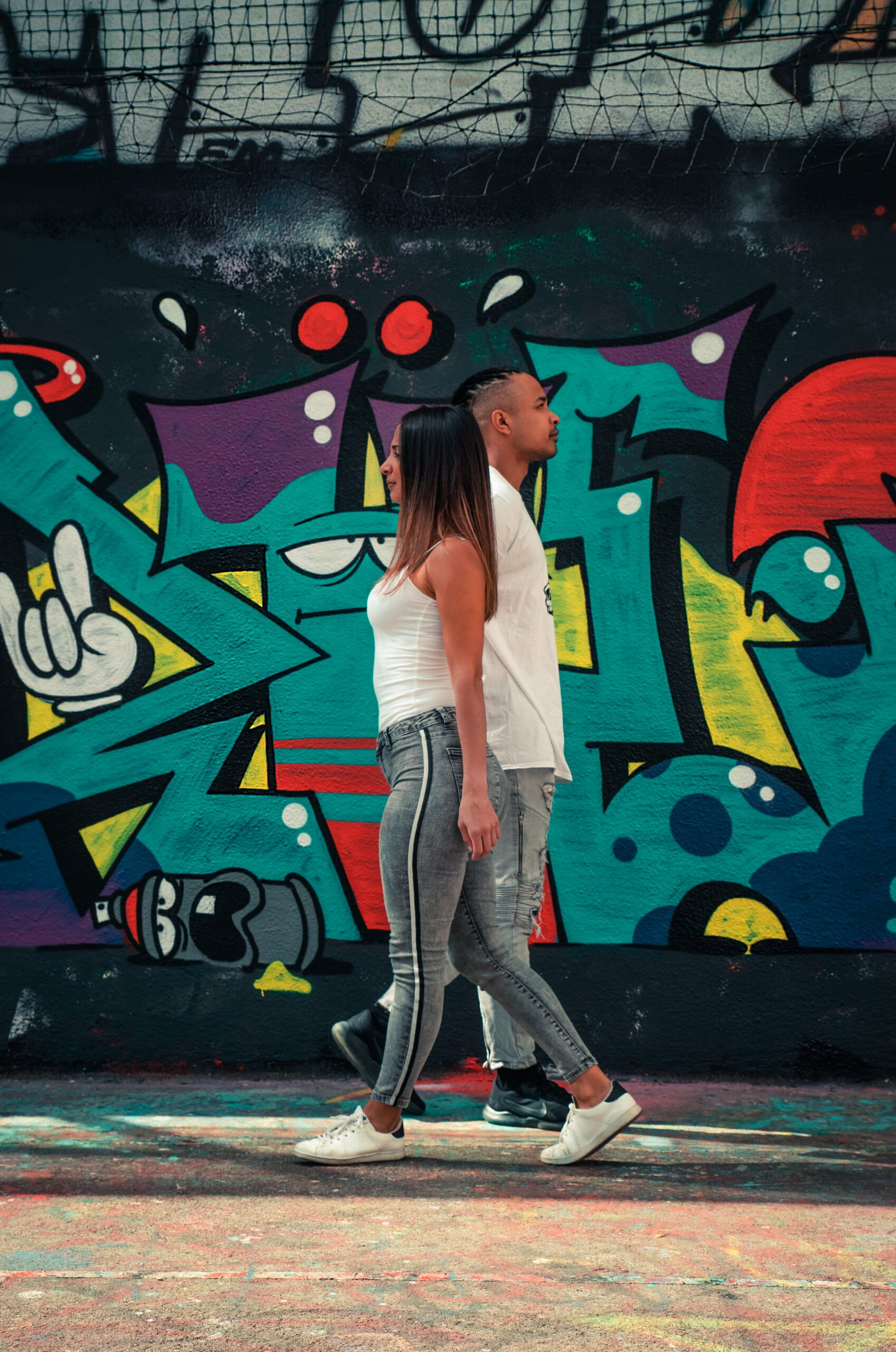 A woman and a man walking past each other in front of wall covered in graffiti