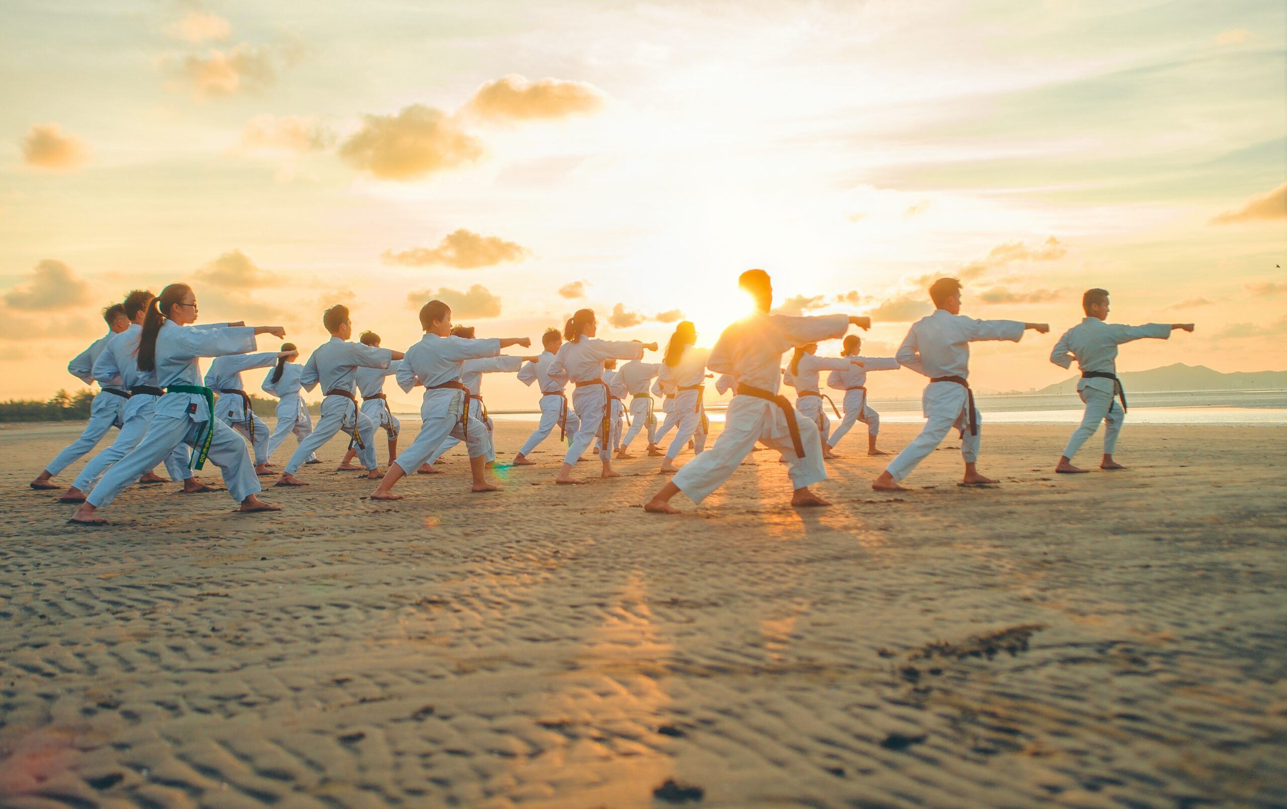 a group of people doing karate on a sandy beach at sunrise