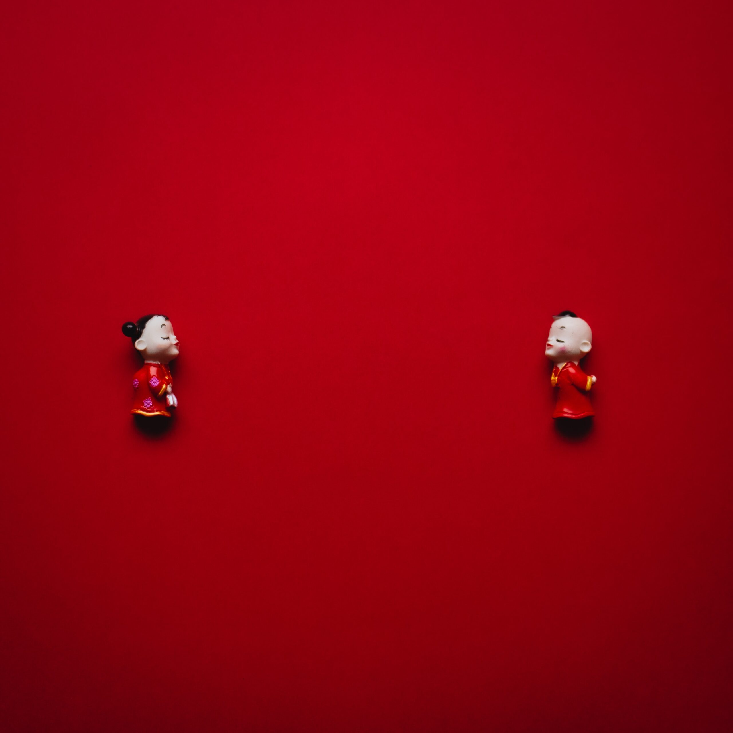 2 dolls facing each other on a red background